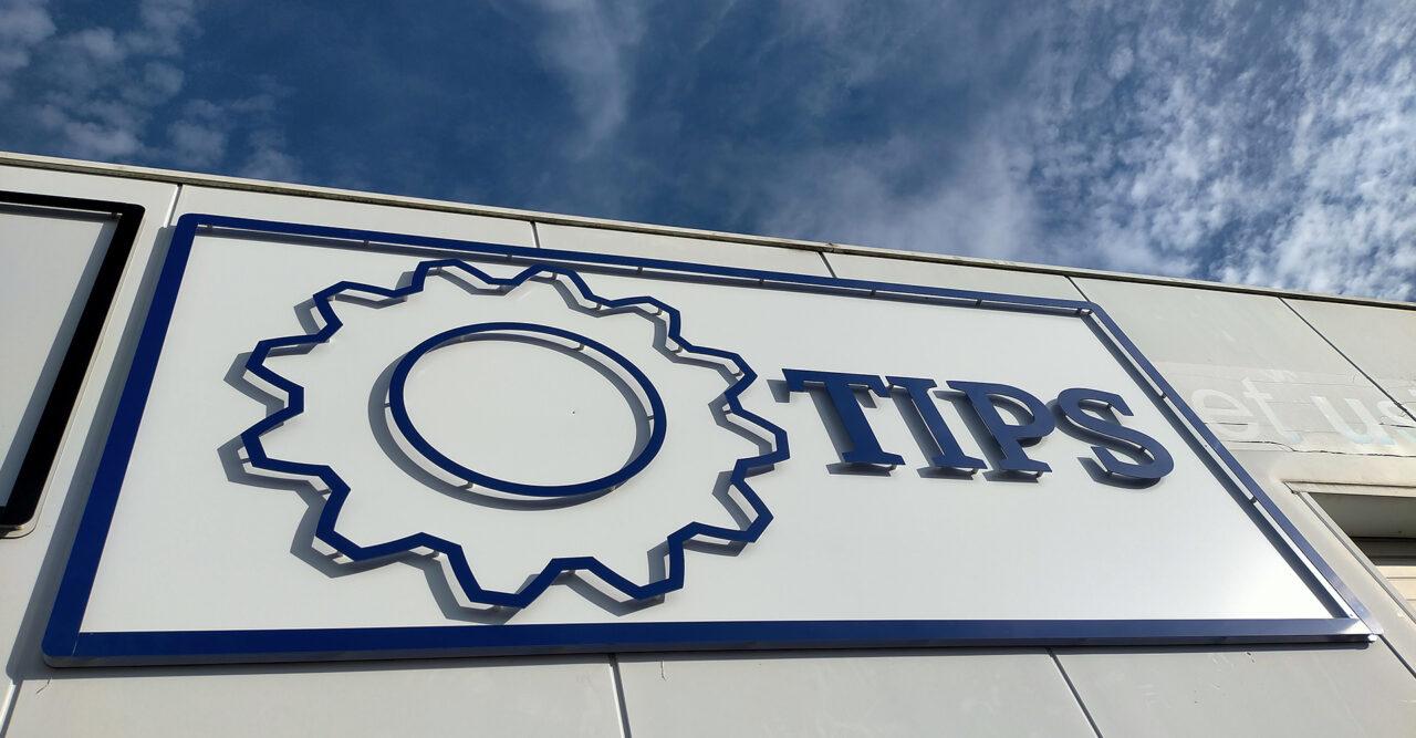 Enseigne TIPS à l'entrée de l'atelier, réaliser par nos soins avec une découpe sur mesure en matières tendres (aluminium, plastique) de couleur blancs et bleus
