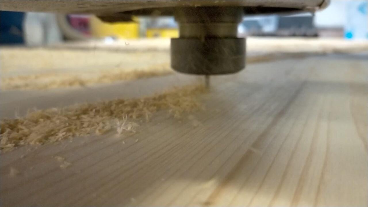Vidéo d'une découpe CNC 3 axes dans du bois. La fraise tourne et avance dans le bois en suivant un fichier numérique pour réaliser une pièce sur mesure
